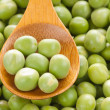 Fresh grren peas on wooden spoon - Stock Photo