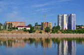 Block of flats and buildings on river bank — Stock Photo