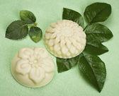 Handgemaakte zeep op een groene achtergrond met bladeren van rozen — Stockfoto