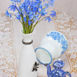Bluebel, vase and teapot on a lace tablecloth, still life — Stock Photo