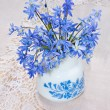 Bluebel in vase on a lace tablecloth, still life — Stock Photo