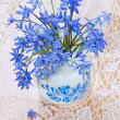 Bluebel in vase on a lace tablecloth, still life - Stock Photo