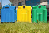 Three recycling bins in a city — Stock Photo
