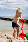 Boy dig in sand on beach — Stock Photo