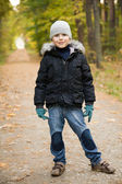 Smiling boy in autumn forest — Stock Photo