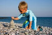 小石のビーチに石のスタックを構築のスーツを泳ぐの少年 — ストック写真
