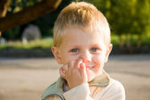 Boy picking his nose outdoors — Stock Photo