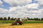трактор, уборки поле пшеницы в летний день — Стоковое фото