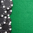 Stock Photo: Red gambling chips on green felt background with copy space