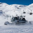 Snowcat and skilift in alps - Stock Photo