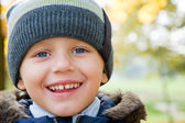 Boy smiling in autumn day — Stock Photo