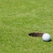 Stock Photo: Golf ball close to hole