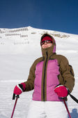 Woman skier in ski suit standing in front of mountain — Foto Stock