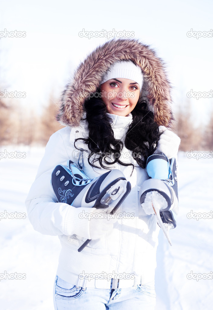 Beautiful brunette girl wearing warm winter clothes going to ice skate — Stock Photo #7971652
