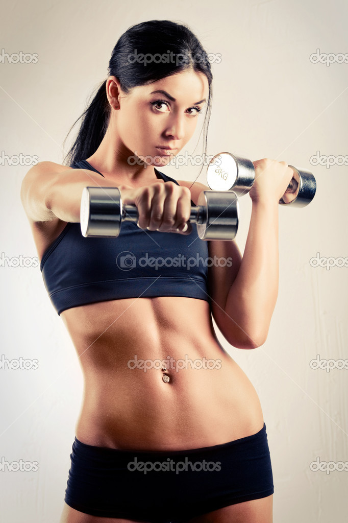 Studio portarit of a beautiful sporty muscular woman working out with two dumbbells  Stock Photo #8229439