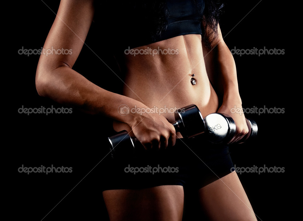 Waist and hands of a beautiful sporty muscular woman working out with two metal dumbbells, isolated against black background (focus on the belly)  Stock Photo #8229451