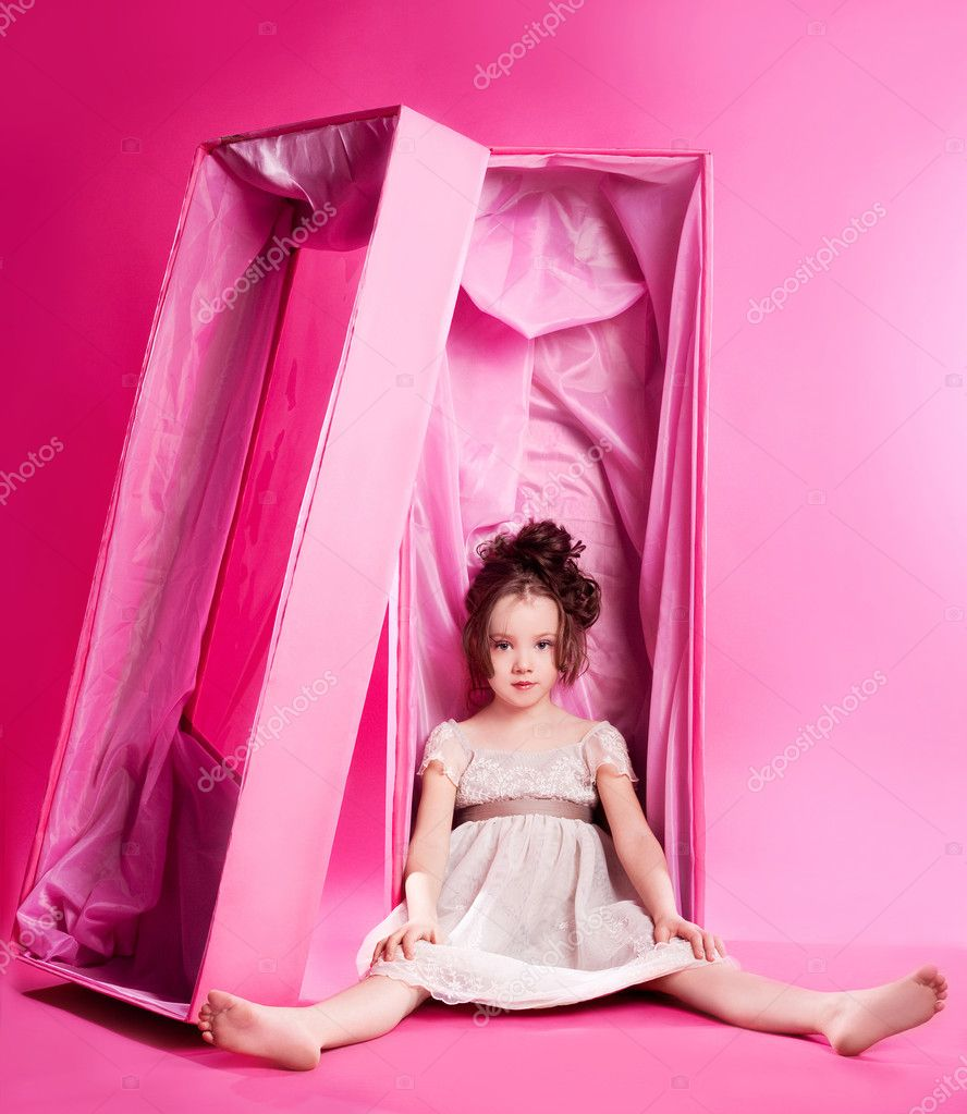 Cute six year old girl as an alive doll in the pink box,  against pink studio background  Stock Photo #8560384
