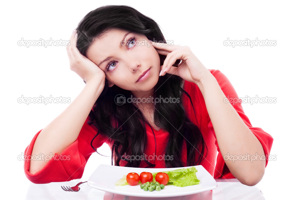 Upset young woman keeping a diet and eating vegetables in the kitchen at home — Stock Photo #8683333