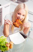 Woman eating chicken — Stock Photo