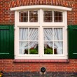 Stock Photo: Old retro window with shutters on red brick house