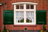 Velha retrô janela com persianas na casa de tijolo vermelho — Foto Stock