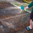 Man watering the ground - Stock Photo