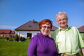 Senior couple in front of the house — Stock Photo