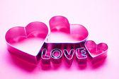 Cuori e amore testo lettere su sfondo rosa — Foto Stock
