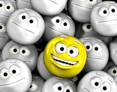 Happy laughing emoticon face among others — Stock Photo