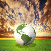 Planet Earth model on green field at sunset — Stock Photo