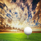 Playing golf. Ball on tee, golf field at sunset — Stock Photo