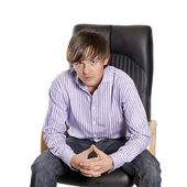 Young, handsome man sitting on a chair — Stock Photo