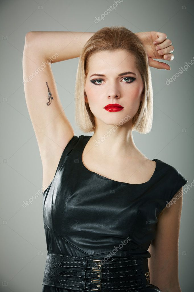 Portrait of young woman with gun tattoo on her arm — Stock Photo #8856882