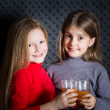 Two little girls holding glasses and drinking orange fruit — Stock Photo