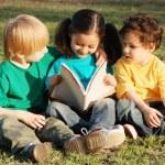 çocuk parkında bir çim üzerinde kitap ile grup — Stok fotoğraf