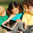 Group of children with the book on a grass in park - Foto de Stock  