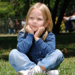 The little girl sitting on a grass in park — Stock Photo