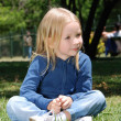 Stock Photo: The little girl sitting on a grass in park