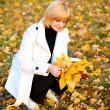 Portrait of pretty woman in autumn park — Stock Photo