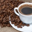 Coffee cup close-up over dark roasted coffee beans — Stock Photo