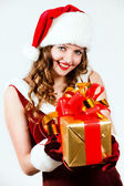 Beautiful woman in a red dress and hat of Santa with a big gift — Stok fotoğraf