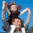 Stock Photo: Father and daughter against sky