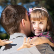 Stock Photo: Beautiful little girl hugging embracing her father