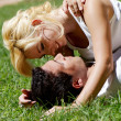 Happy young couple playing at park in grass — Stock Photo #9499475