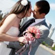 Happy newly-married couple against a city — Stock Photo #9500876