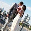 Happy newly-married couple against a city — Stock Photo #9500879