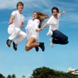 Group of friends in a jump against a city and the sky — Stock Photo #9502012