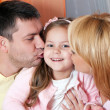 Parents kissing daughter portrait looking very happy — Stok fotoğraf