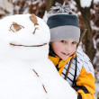 Boy and a snowman - a winter holiday — Stock Photo