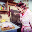 The silly housewife with butcher in hands and carcass of a hen — Stock Photo #9506262